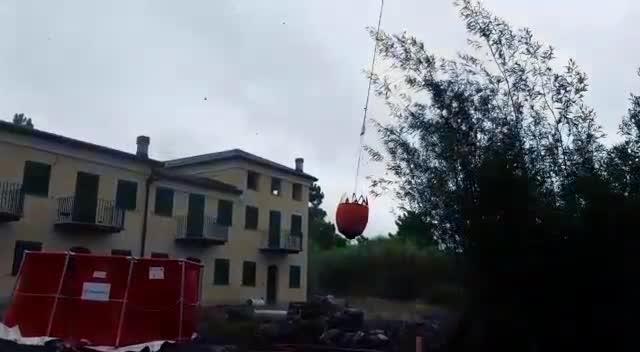 """Gli elicotteri dei vigili del fuoco si """"ricaricano"""" nella vasca allestita vicino all'incendio"""